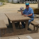 This is an exposed aggregate concrete table, which weighs over 1,100 pounds. These beautiful tables will be placed on concrete slabs and can survive flooding.